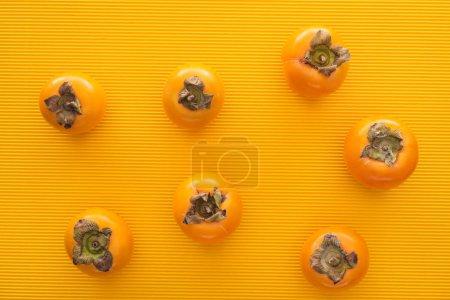 Photo pour Vue de dessus des kakis ensemble orange sur fond jaune - image libre de droit