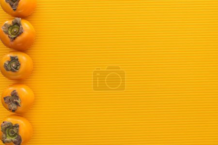 Photo for Top view of orange persimmons on yellow background with copy space - Royalty Free Image