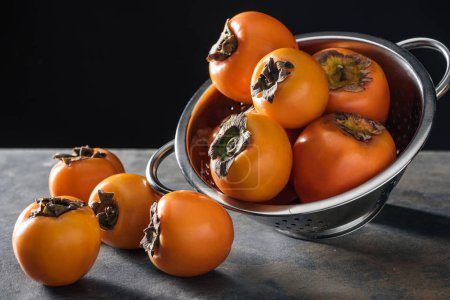 Photo for Orange and whole persimmons in colander on stoned table - Royalty Free Image