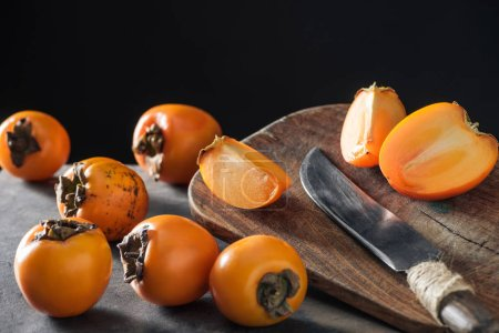 Photo for Ripe and orange persimmons on cutting board with knife - Royalty Free Image