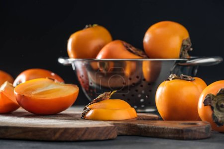Photo for Selective focus of orange persimmons on cutting board and in colander - Royalty Free Image