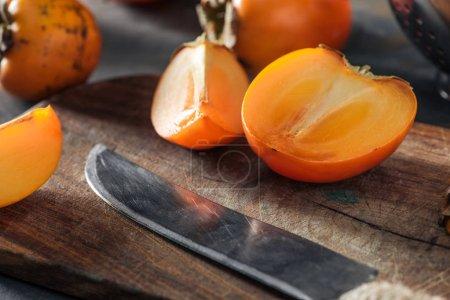 Photo pour Kakis orange et tranchés sur une planche à découper avec couteau - image libre de droit