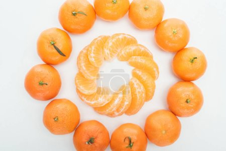 Photo for Flat lay with circles of peeled tangerine slices and whole tangerines on white background - Royalty Free Image