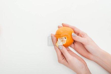 partial view of woman peeling ripe orange tangerine on white background