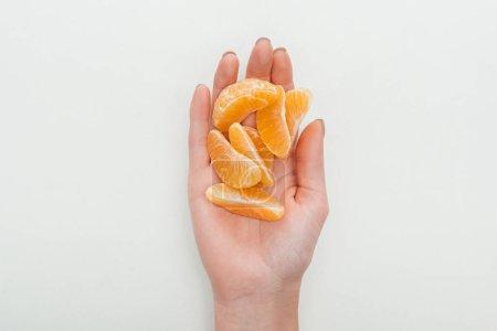 Photo pour Vue partielle de la femme tenant des tranches de mandarine pelées sur fond blanc - image libre de droit