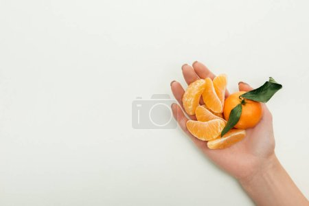 Photo pour Vue partielle de la femme tenant pelées tranches de mandarine et mandarine entier sur fond blanc - image libre de droit