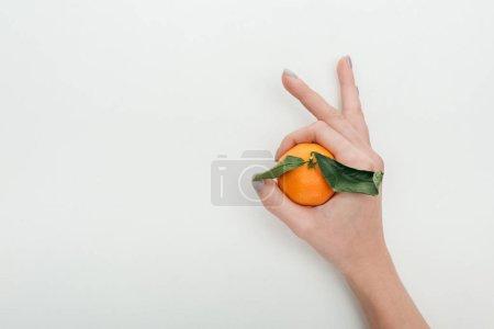 Photo pour Recadrée vue de femme montrant signe OK avec mandarine dans la main - image libre de droit