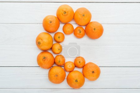 Photo for Top view of letter C made of fresh tangerines on wooden white surface - Royalty Free Image