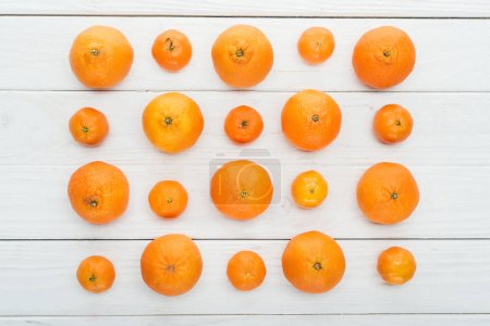 Photo pour Lay plat avec grandes et petites tangerines mûrs sur fond blanc en bois - image libre de droit