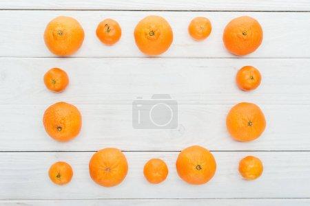 Foto de Vista superior de marco cuadrado de mandarinas naranja maduras en superficie blanco madera - Imagen libre de derechos