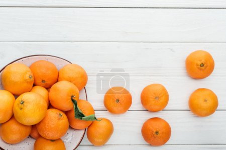Photo for Top view of ripe tangerines scattered from plate on wooden white background - Royalty Free Image
