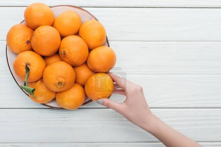 Photo for Partial view of female hand near plate with tangerines on wooden white background - Royalty Free Image