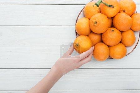 Photo pour Vue partielle de la main féminine près de la plaque avec des mandarines sur fond blanc en bois avec espace de copie - image libre de droit