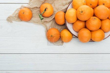 Photo pour Vue de dessus de mandarines dispersées près de la plaque avec tissu sur fond blanc en bois - image libre de droit
