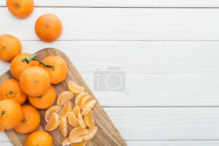Photo for Top view of peeled tangerine slices and whole ripe tangerines on wooden chopping board - Royalty Free Image