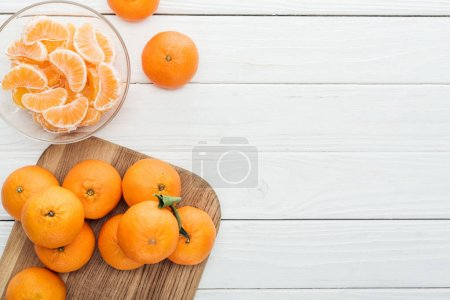 top view of peeled tangerine slices in glass bowl and whole ripe tangerines on wooden chopping board