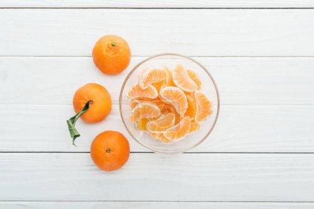 Photo pour Vue de dessus des tranches de mandarine pelées dans le bol en verre et des mandarines mûrs tout autour sur fond blanc en bois - image libre de droit
