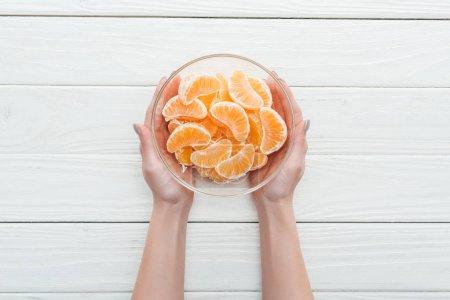 Photo pour Vue recadrée de femme tenant le bol en verre avec des tranches de mandarine sur fond blanc en bois - image libre de droit