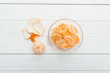 Photo pour Vue de dessus des tranches de mandarine pelées dans le bol en verre et peel sur fond blanc en bois - image libre de droit