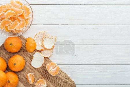 Photo pour Vue de dessus de mandarines pelées sur planche à découper en bois sur une table en bois blanc - image libre de droit