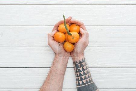 Photo pour Vue recadrée d'un homme tatoué tenant un tas de mandarines sur une surface en bois blanc - image libre de droit