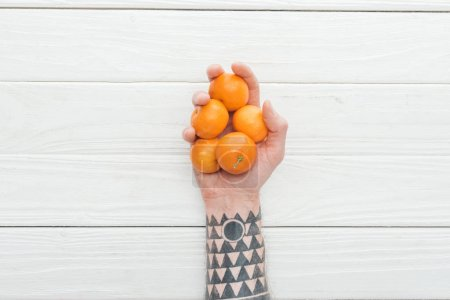 Photo pour Vue recadrée d'un homme tatoué tenant un tas de mandarines à la main sur une surface en bois blanc - image libre de droit