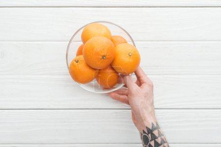 Photo pour Vue recadrée d'un homme tenant un bol en verre avec des mandarines mûres sur une surface en bois - image libre de droit