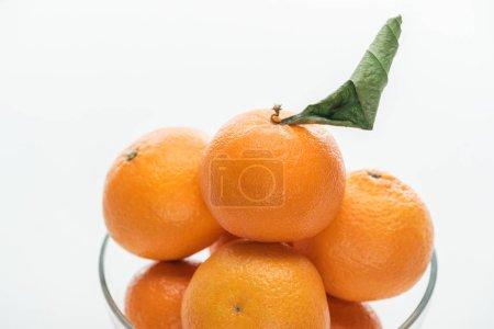 Photo pour Gros plan du pieu de mandarines dans bol en verre sur fond blanc - image libre de droit