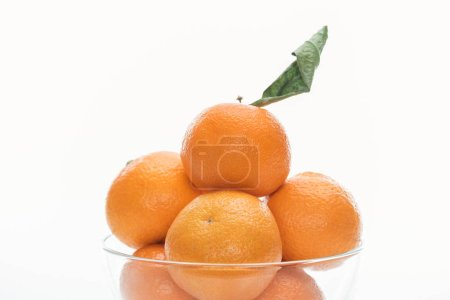 Photo pour Gros plan du pieu de mandarines dans un bol de verre isolé sur blanc - image libre de droit