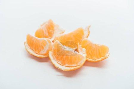 Photo pour Tranches de mandarine mûres avec écorce sur fond blanc - image libre de droit