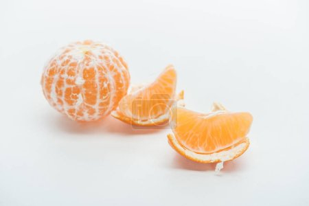 tangerine slices with peel and whole fruit on white background