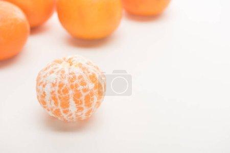 selective focus of ripe peeled whole tangerine on white background