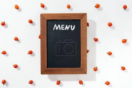 Photo pour Vue du dessus de la planche à craie avec lettrage de menu parmi les tomates cerises - image libre de droit