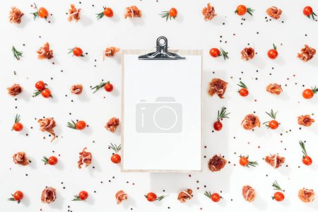 Photo for Top view of blank clipboard with cherry tomatoes, leaves, spices and prosciutto - Royalty Free Image