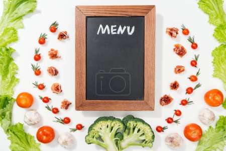 Photo for Top view of chalk board with menu lettering among tomatoes, lettuce leaves, prosciutto, broccoli and garlic - Royalty Free Image
