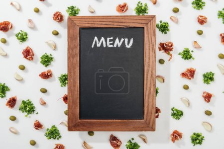 Photo for Top view of chalk board with menu lettering among prosciutto, olives, garlic cloves and greenery - Royalty Free Image