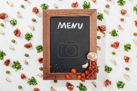 Photo pour Vue de dessus du Conseil de la craie avec le lettrage de menu parmi les jambon, olives, gousses d'ail, verdure et tomates cerises - image libre de droit