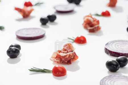 Photo for Selective focus of prosciutto near cherry tomatoes with rosemary twigs near red onion rings and black olives on white background - Royalty Free Image
