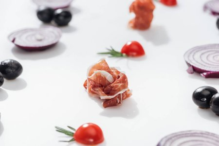 Photo pour Selective focus of tasty prosciutto near cherry tomatoes with rosemary twigs near red onion rings and black olives on white background - image libre de droit