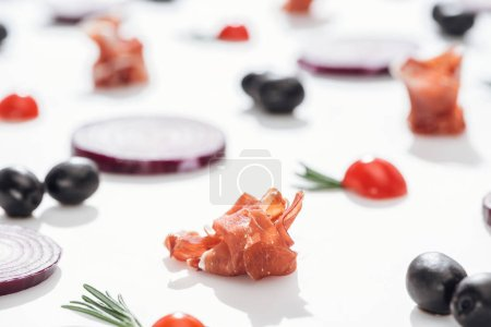 Photo for Selective focus of delicious prosciutto near cherry tomatoes with rosemary twigs and red onion rings on white background - Royalty Free Image