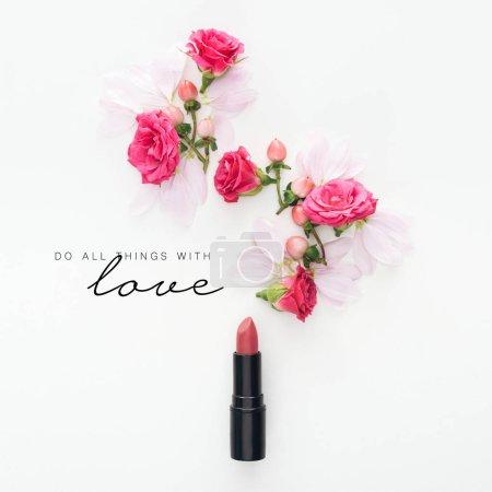 Photo pour Vue de dessus de la composition avec des roses, des bourgeons et des pétales avec du rouge à lèvres sur fond blanc avec faire toutes choses avec l'amour lettrage - image libre de droit