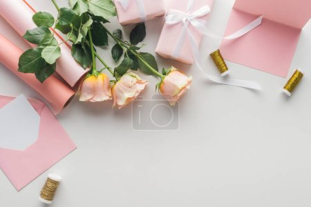 Photo for Top view of pink roses, rolls of paper, wrapped gifts and envelope on grey background - Royalty Free Image