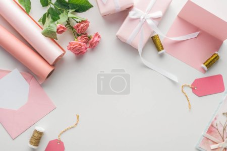 Photo for Top view of pink roses, rolls of paper, wrapped gifts, envelope and greeting card on grey background - Royalty Free Image