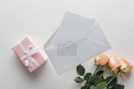 Photo for Top view of pink roses, wrapped gifts, envelope and card on grey background - Royalty Free Image