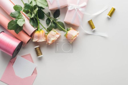 Photo for Top view of roses, rolls of paper, wrapped gifts, envelope, greeting card and spools of thread on grey background - Royalty Free Image