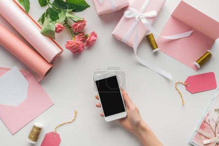 Photo for Cropped view of woman holding smartphone near roses, rolls of paper, wrapped gifts, envelope, greeting card and spools of thread on grey background - Royalty Free Image