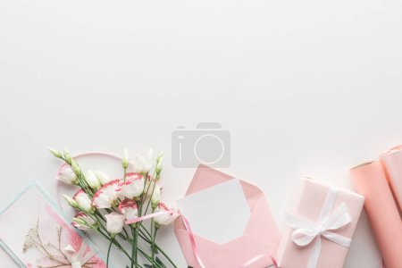 Photo for Top view of pink eustoma, rolls of paper, wrapped gifts, envelope and greeting card on grey background - Royalty Free Image
