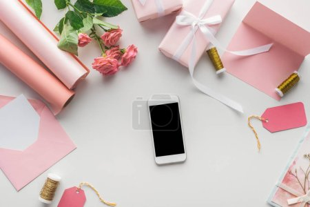 top view of smartphone near roses, rolls of paper, wrapped gifts, envelope and spools of thread on grey background