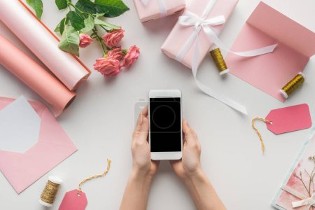 Photo for Cropped view of woman holding smartphone near roses, rolls of paper, wrapped gifts, envelope, card and spools of thread on grey background - Royalty Free Image