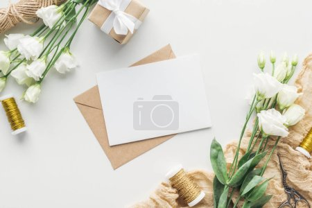 Photo for Top view of eustoma, wrapped gift, envelopes with empty card, spools of thread and cloth on grey background - Royalty Free Image
